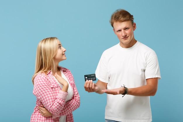 Joven pareja alegre dos amigos chico y mujer en blanco rosa camisetas en blanco vacías posando