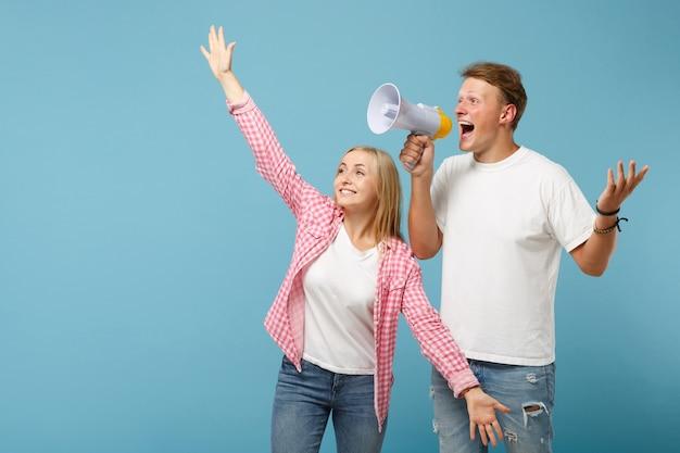 Joven pareja alegre dos amigos chico y mujer en camisetas blancas rosas vacías posando