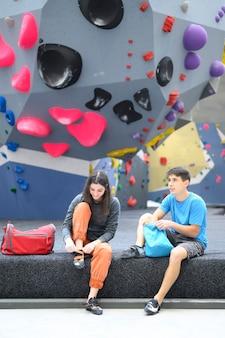 Joven pareja alegre en el gimnasio de búlder. hombre y mujer joven hablando antes de la escalada en roca
