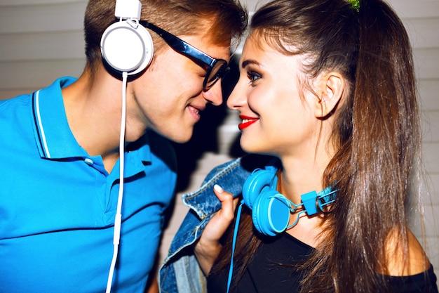 Joven pareja alegre volviéndose locos juntos, caras divertidas emocionales, fiesta urbana, escuchando música en elegantes auriculares grandes, pareja hipster enamorada.