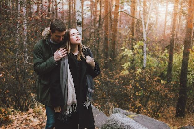 Joven pareja de amigos del amor vestidos de estilo casual caminando juntos en el bosque del parque natural en la temporada de frío. sensibilidad al concepto de naturaleza.