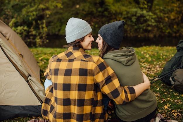 Joven pareja amorosa abrazándose en el bosque