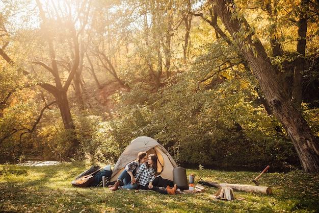 Joven pareja amorosa en acampar en el bosque