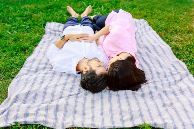 Joven pareja amorosa acostado juntos disfrutando de la cercanía