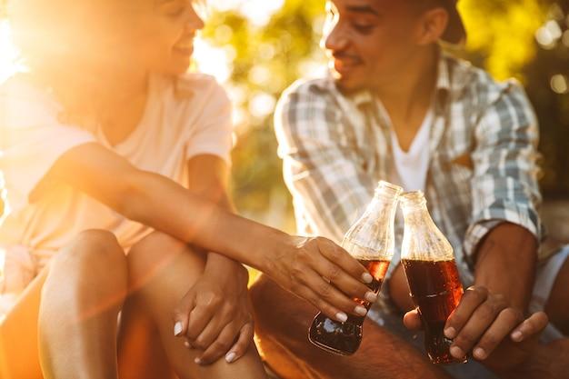Joven pareja amorosa africana sentada al aire libre en el parque bebiendo refrescos.