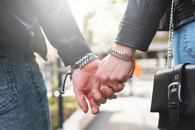 Joven pareja amorosa cogidos de la mano durante una fecha al aire libre