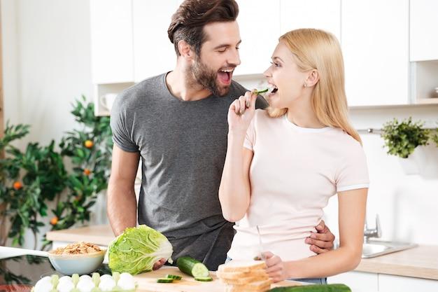 Joven pareja amorosa divertida de pie en la cocina y cocinar