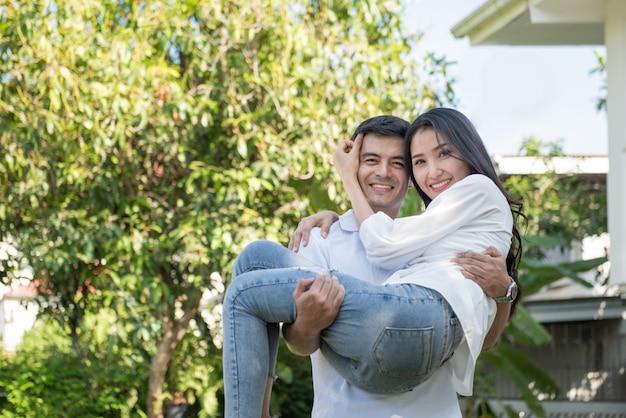 Joven pareja amorosa divertirse en el parque. el novio caucásico continúa con su novia asiática en brazos en el patio delantero de la casa.