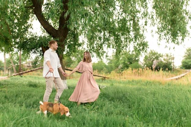 Joven pareja amorosa divirtiéndose y corriendo sobre la hierba verde en el césped con su perro doméstico raza beagle