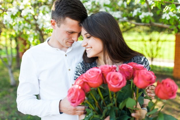Joven pareja amorosa enamorada, mujer sosteniendo flores, feliz y disfruta de la hermosa naturaleza