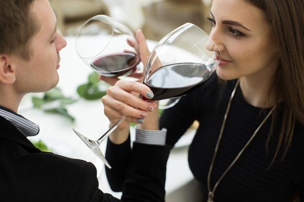 Joven pareja amorosa feliz celebrando con vino tinto en el restaurante. fraternidad