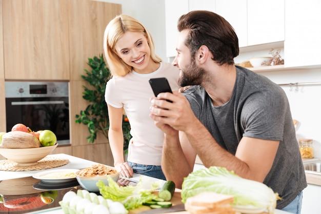 Joven pareja amorosa feliz cocinando juntos usando el teléfono