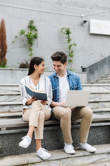 Joven pareja amorosa increíble gente de negocios colegas al aire libre afuera en pasos usando el libro de lectura de la computadora portátil.