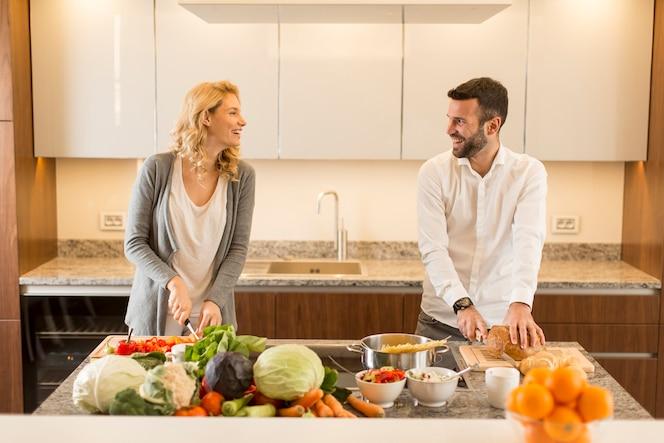 Joven pareja amorosa preparando sabrosa comida en una cocina moderna