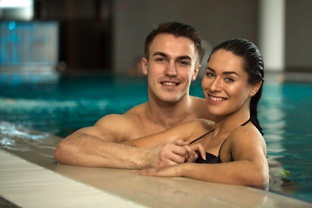 Joven pareja amorosa que se relaja en la piscina del spa juntos