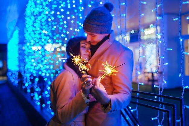 Joven pareja amorosa quema de bengalas por iluminación de vacaciones. concepto de navidad y año nuevo.