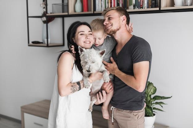 Joven pareja amorosa con su lindo hijo y su perro blanco en casa