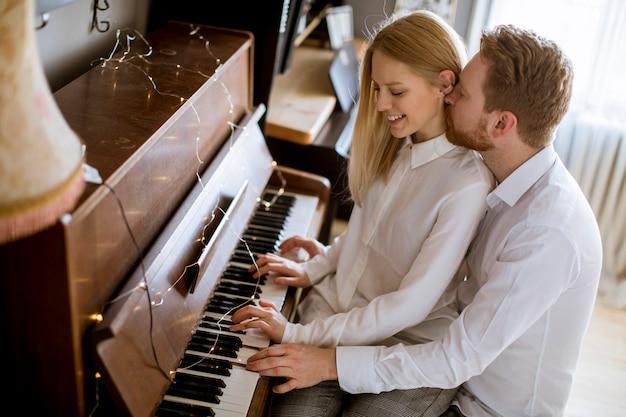 Joven pareja amorosa tocando el piano