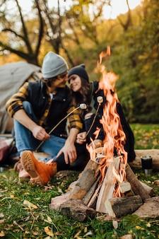 Joven pareja amorosa de turistas relajándose cerca del fuego en la naturaleza