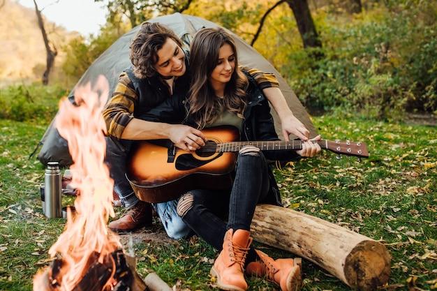 Joven pareja amorosa de turistas relajándose cerca de la hoguera en la naturaleza