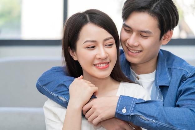 Joven pareja asiática abrazándose felizmente en casa