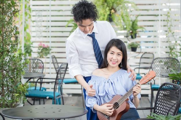 Joven pareja asiática en el amor tocando la guitarra, feliz adolescente de raza mixta