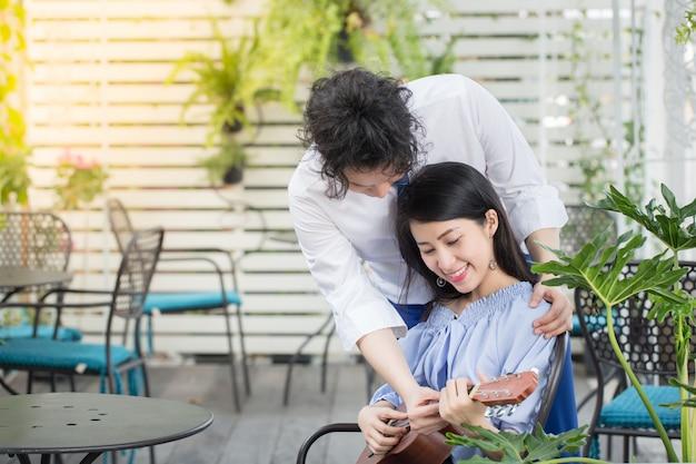 Joven pareja asiática en el amor tocando la guitarra, feliz concepto de adolescente de raza mixta