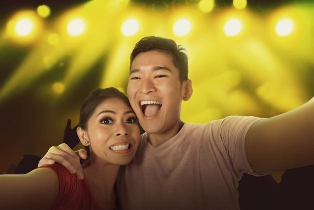 Joven pareja asiática autofoto con la multitud