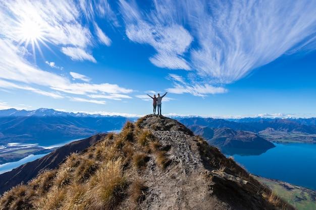 Joven pareja asiática celebrando el éxito en roy's peak lake wanaka nueva zelanda