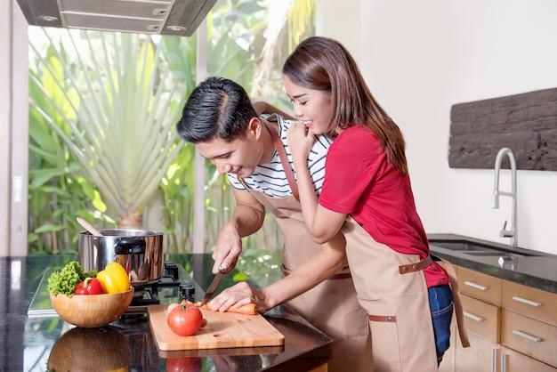 Joven pareja asiática cocinando en la cocina