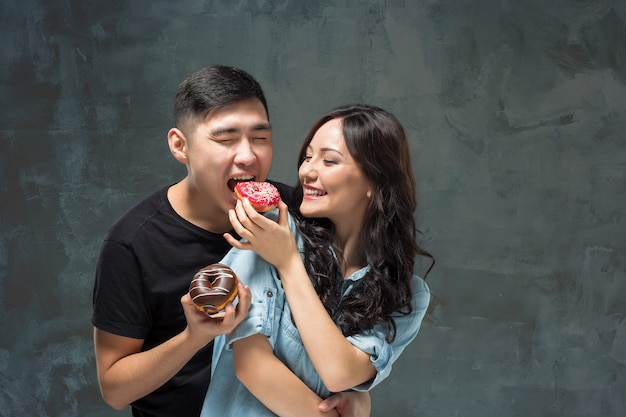 Joven pareja asiática disfruta comiendo dulce donut colorido