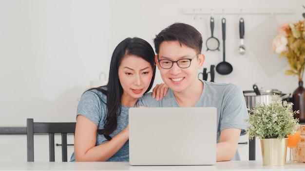 Joven pareja asiática disfruta de compras en línea en la computadora portátil en casa. estilo de vida joven esposo y esposa felices compran comercio electrónico después de desayunar en la cocina moderna de la casa por la mañana.