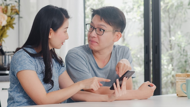 Joven pareja asiática disfruta de compras en línea en el teléfono móvil en casa. estilo de vida joven esposo y esposa felices compran comercio electrónico después de desayunar en la cocina moderna de la casa por la mañana.