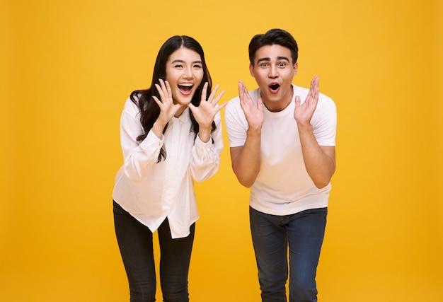 Joven pareja asiática hombre y mujer feliz y gritar anuncian sobre fondo amarillo.