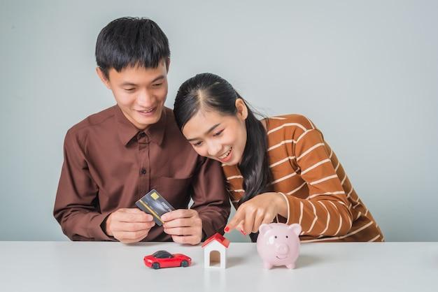 Joven pareja asiática con hucha y casa de juguete y coche