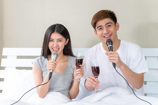 Joven pareja asiática llena feliz sosteniendo una copa de vino y canta una canción fiesta de karaoke celebra en el dormitorio