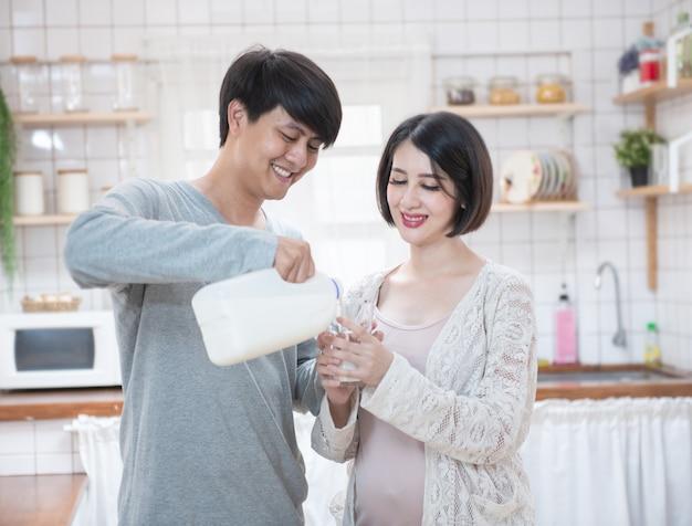 Joven pareja asiática con una mujer embarazada bebiendo leche