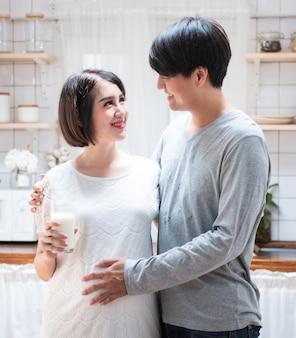 Joven pareja asiática con papá abrazando a mamá en la cocina