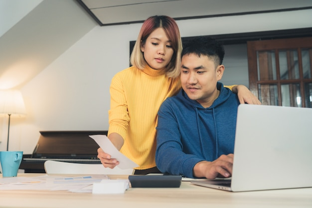 Joven pareja asiática que maneja las finanzas, revisando sus cuentas bancarias usando una computadora portátil
