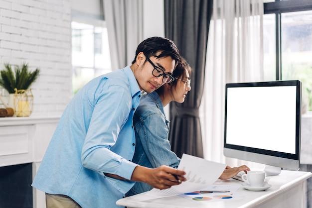 Joven pareja asiática relajante usando computadora de escritorio trabajando y videoconferencia reunión chat en línea.