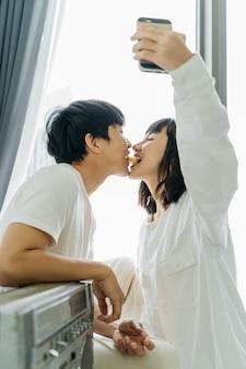 Joven pareja asiática tomando un selfie mientras juega