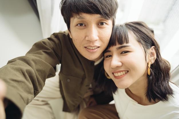Joven pareja asiática tomando un selfie con smartphone
