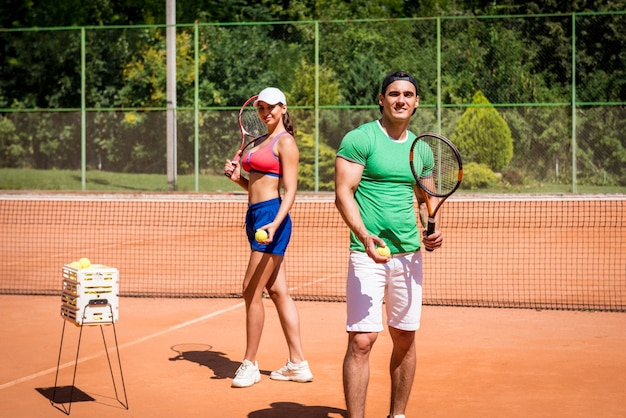 Joven pareja atlética jugando al tenis en la cancha.