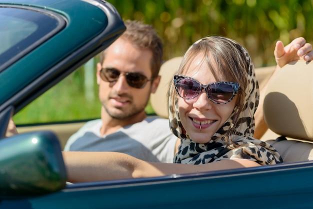 Una joven pareja en un auto convertible