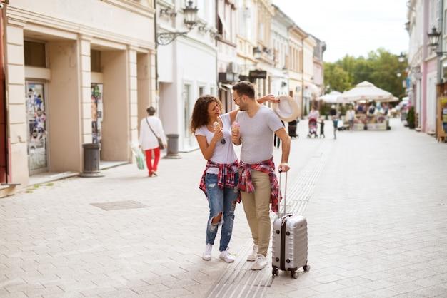 Joven pareja aventurera está caminando por la calle comiendo helados hablando y divirtiéndose.