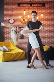 Joven pareja bailando música latina: bachata, merengue, salsa. dos elegancia posan en café con paredes de ladrillo