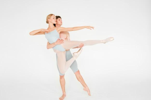 Joven pareja de bailarines de ballet moderno posando en el estudio