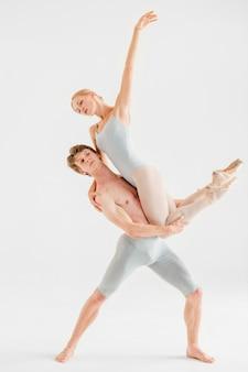 Joven pareja de bailarines de ballet moderno posando sobre estudio blanco.