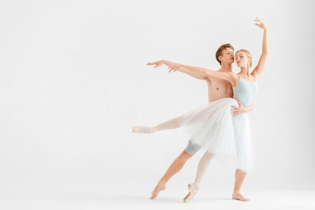 Joven pareja de bailarines de ballet moderno posando sobre fondo blanco de estudio