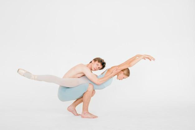 Joven pareja de bailarines de ballet moderno posando sobre pared de estudio blanco.